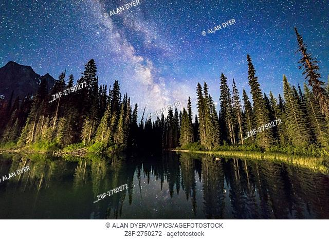 The Milky Way over the side pond at Emerald Lake, Yoho National Park, BC. , from the bridge to the Lodge. Lights from the Lodge illuminate the trees