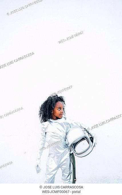 Little girl wearing space suit in front of white background looking around