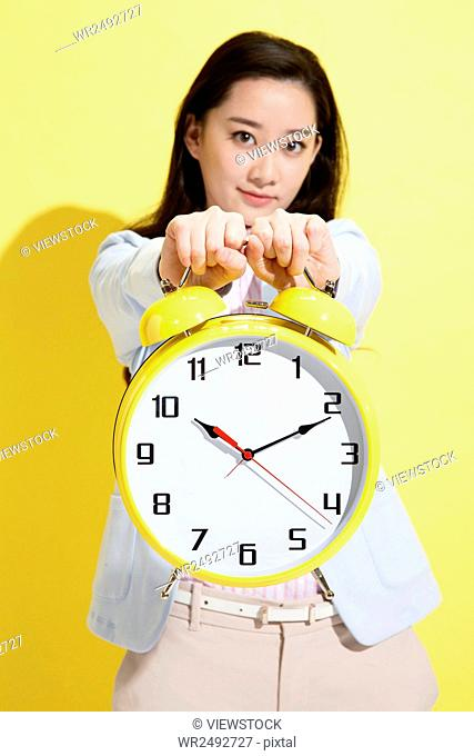 Young business woman holding a clock
