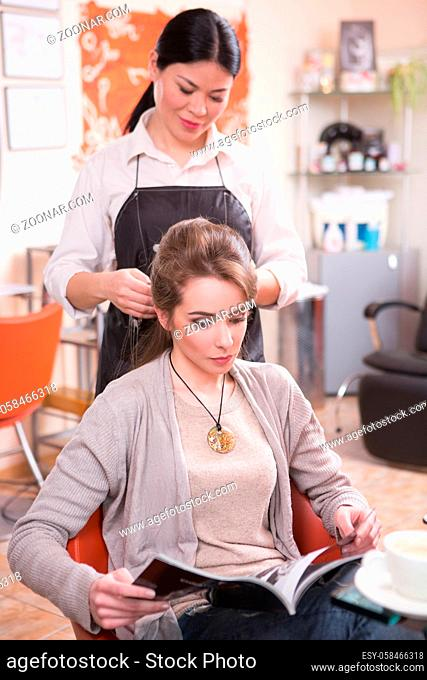 Pretty lady reading magazine while having her hair cut or done by beautiful barber girl in hairdressing saloon