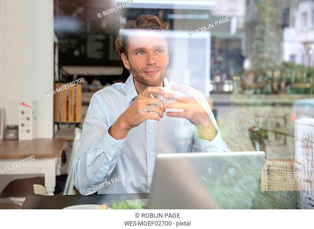 Young businessman with coffee cup and laptop in a cafe