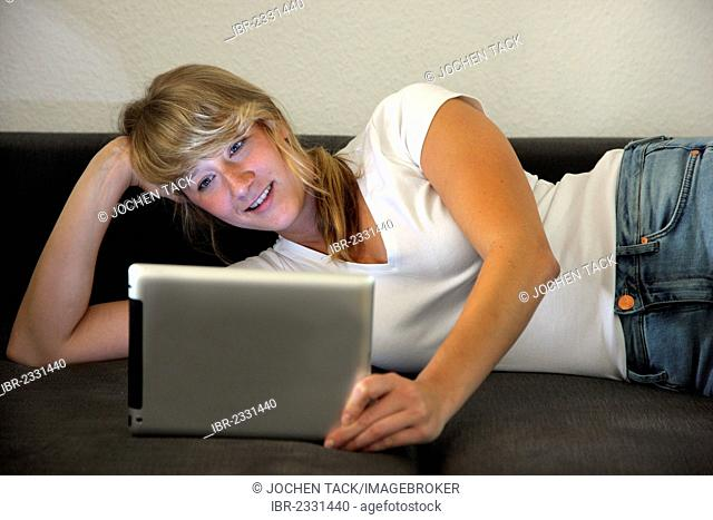 Young woman lying on a sofa surfing the internet, iPad, tablet computer with wireless internet access