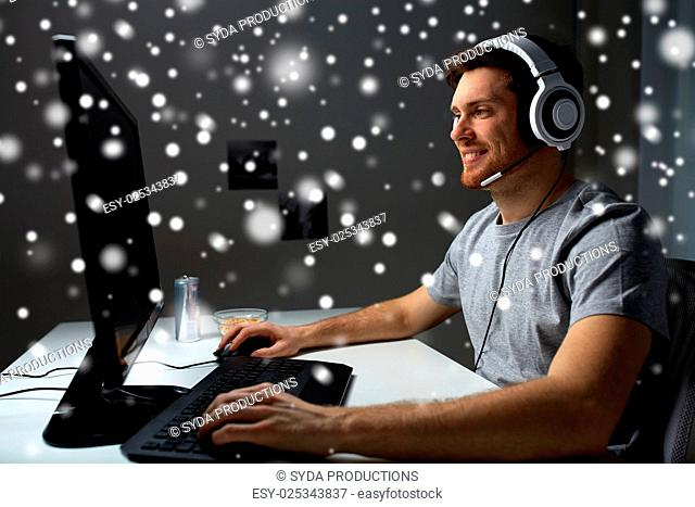 technology, gaming, entertainment, let's play and people concept - happy young man in headset with pc computer playing game at home and streaming playthrough or...