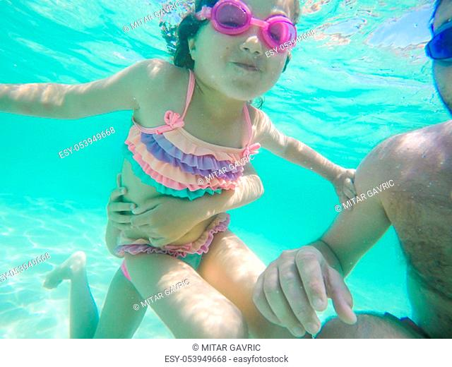 Happy child underwater portrait - Little girl wearing swimming goggles dive and swim in the seawater - Summer vacation fun