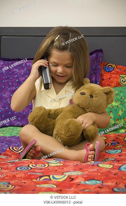 Hispanic girl talking on cordless phone
