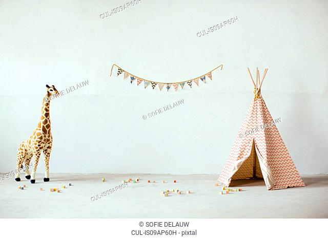 Still life with toy giraffe, teepee and bunting