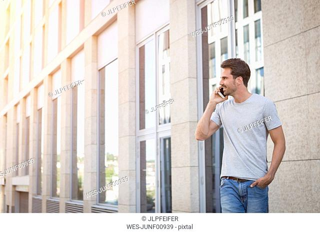 Man walking in the city, making a phone call