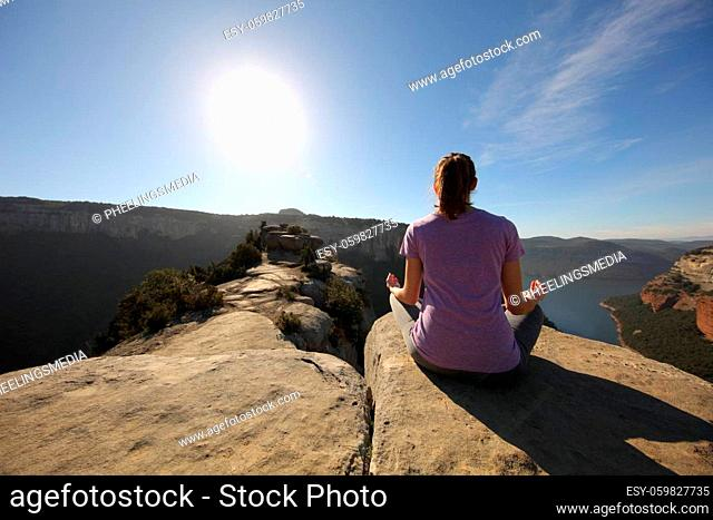 Back view portrait of a person doing yoga exercise in the top of a cliff in the mountain in front of the sun