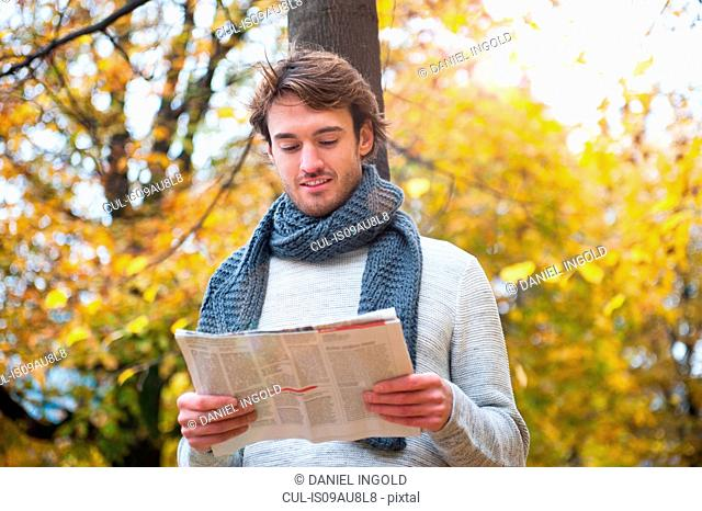 Young man outdoors, in park, reading newspaper