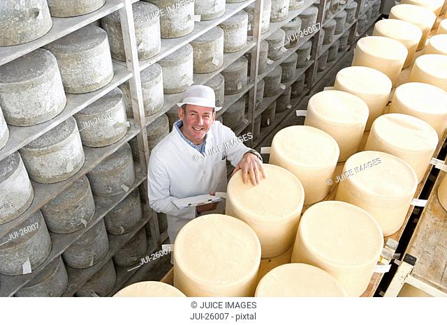 Portrait of smiling inspector with clipboard checking young farmhouse cheddar cheese wheels on shelf in cellar