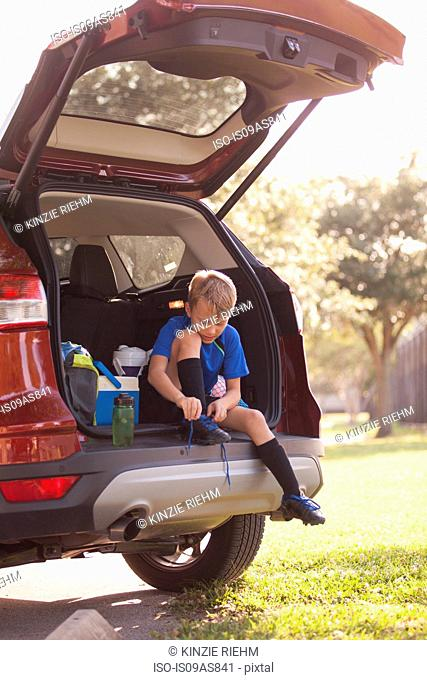 Boy football player sitting in car boot tying football boot laces