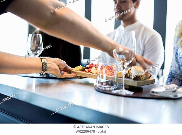 Cropped image of waiter serving food to customers at restaurant