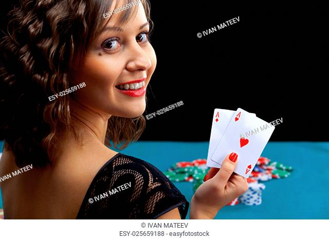 Young woman holding poker cards in front of gambling chips