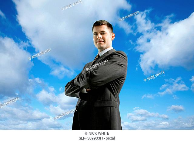 Businessman with crossed arms against sky