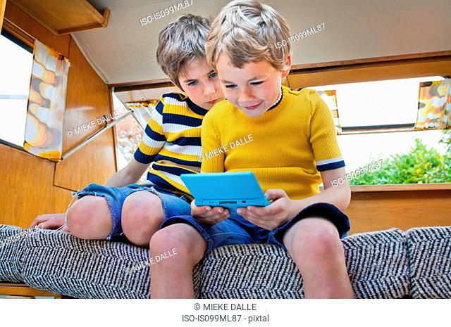 Two boys playing handheld video game