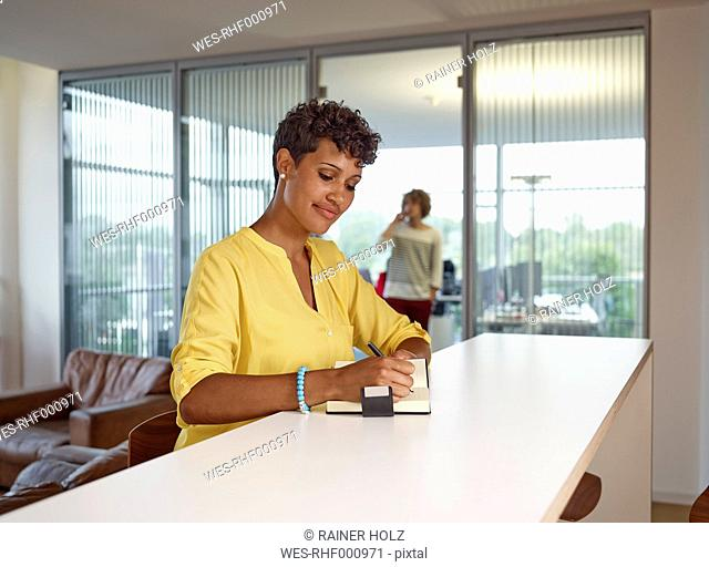 Young woman in office writing in notebook