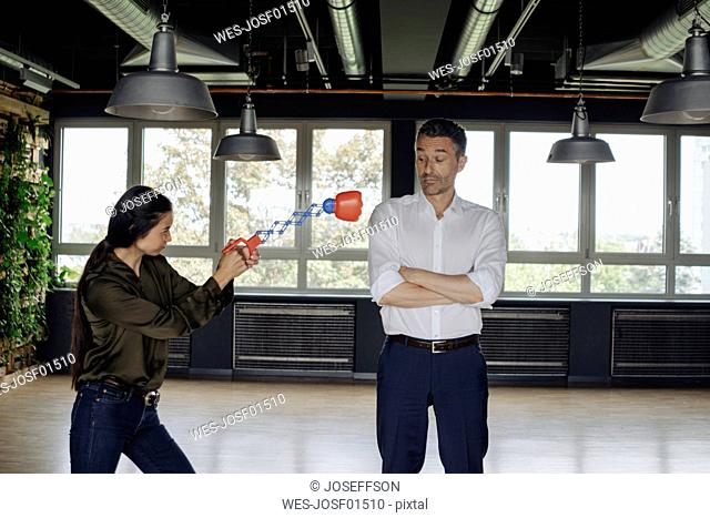 Businesswoman in office hitting businessman with boxing toy
