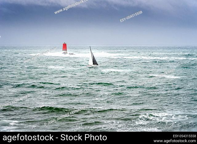 Sailing boat in the sea with bad weather. Boat sailing in the upcoming storm near lighthouse
