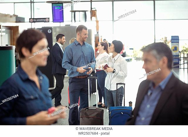 Business people holding boarding pass and using mobile phone