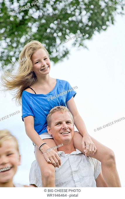 Father with his tween daughter on his shoulders on a windy day