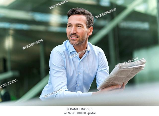 Businessman with newspaper in the city looking around