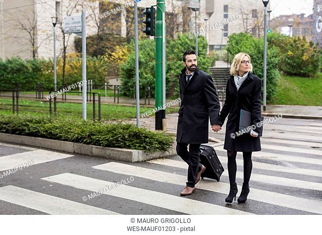 Business couple in the city crossing a street