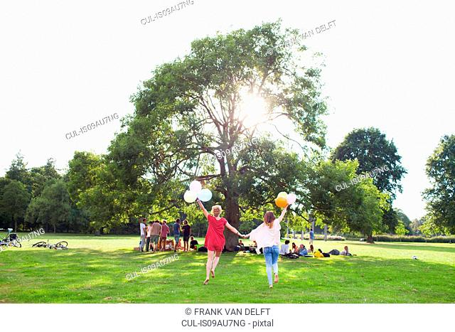 Rear view of two young women dancing with balloons at park party