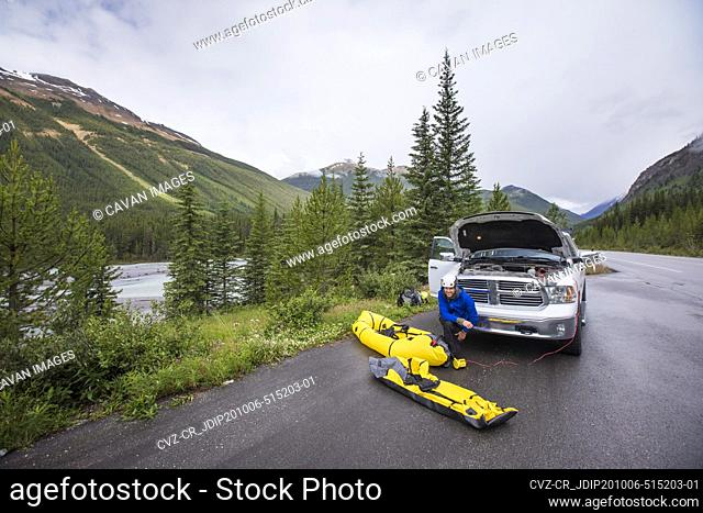 Man using power from truck battery to inflate river kayaks, packrafts
