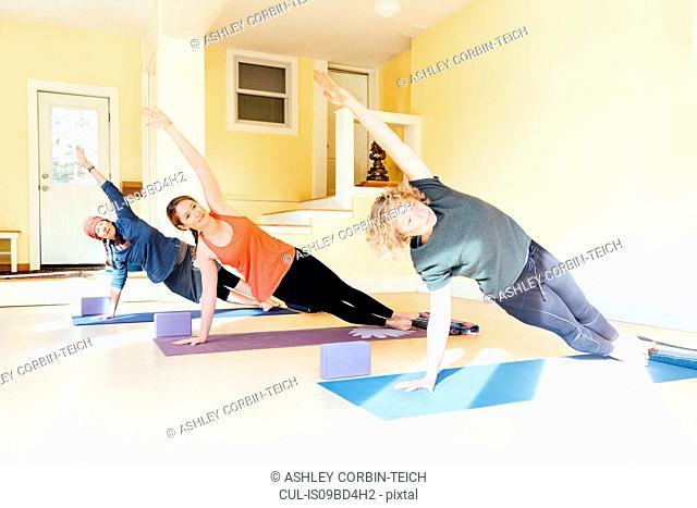 Three women practicing yoga pose in yoga studio