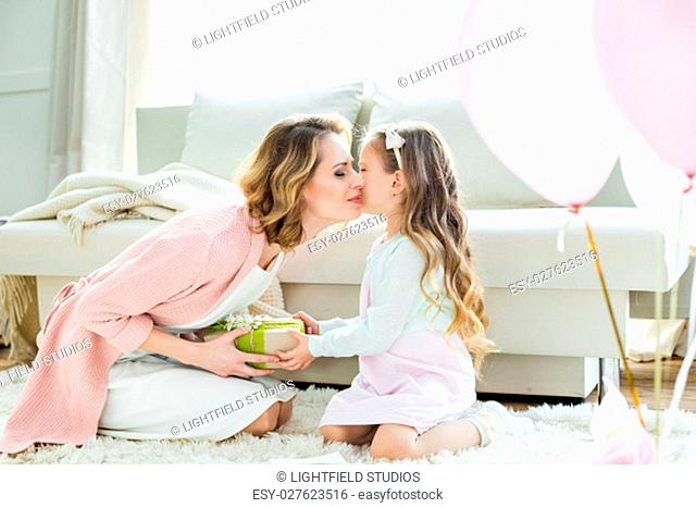 Adorable little girl presenting gift and kissing happy mother on Mothers Day