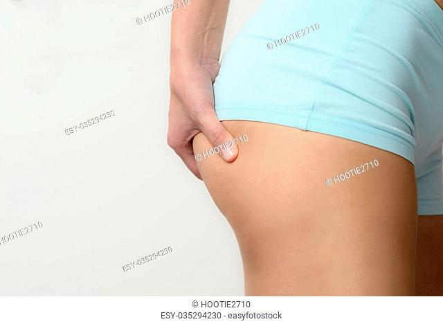 Slender young woman checking for excess weight on her buttocks pinching the muscle between her hands, closeup view of her hand