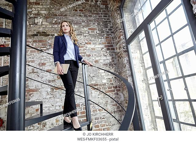 Businesswoman walking down spiral staircase