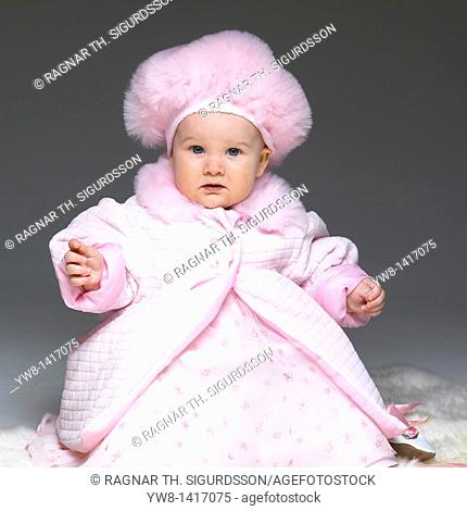 Baby girl in pink dress, coat and hat