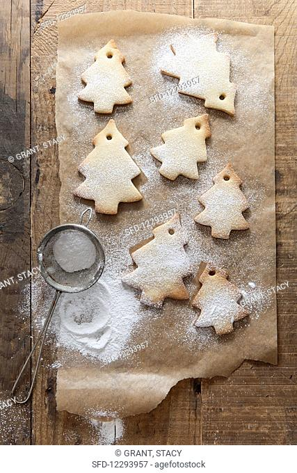 Tree shaped biscuits on baking paper being dusted with icing sugar from a mini sifter on a rustic wooden surface