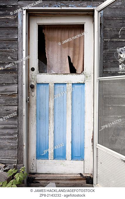An exterior weathered wooden door with a broken window pane found outside an abandoned house in the Parry Sound District of Northern Ontario, Canada