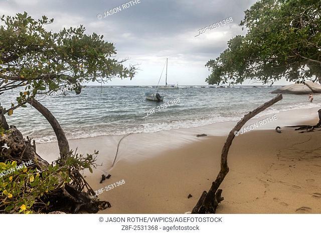 Sailboat and fishing boat anchored behind the protective wall of a rocky reef at Tayrona National Park near Santa Marta, Colombia