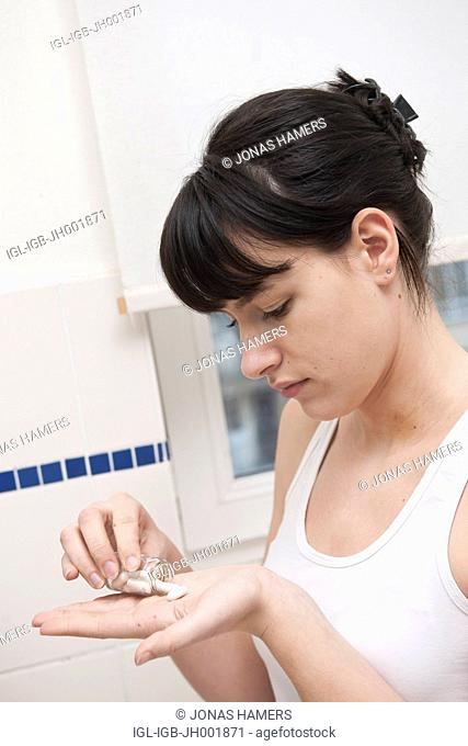 This picture shows a young caucasian woman with brown hair as she got a few homeopathic pills from a tube in her hand