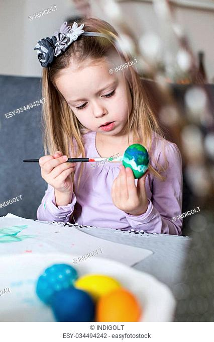 A happy little child coloring easter eggs. Cozy home atmosphere. Easter