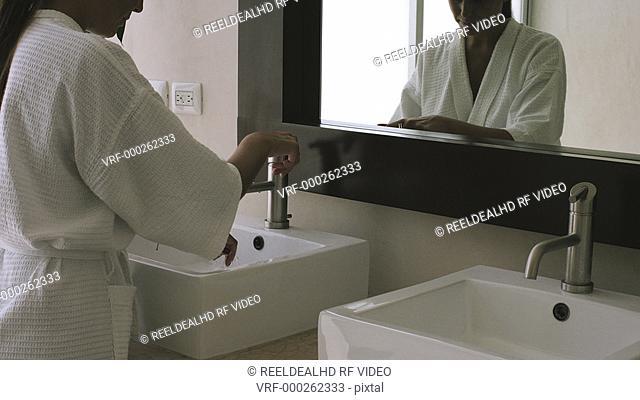 Woman wears bathrobe and washing hands in bathroom