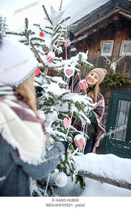 Austria, Altenmarkt-Zauchensee, two young women decorating Christmas tree at wooden house