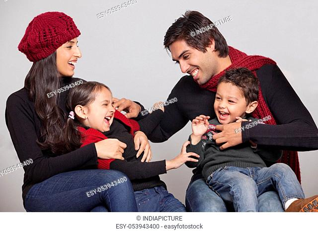 Playful family sitting over grey background
