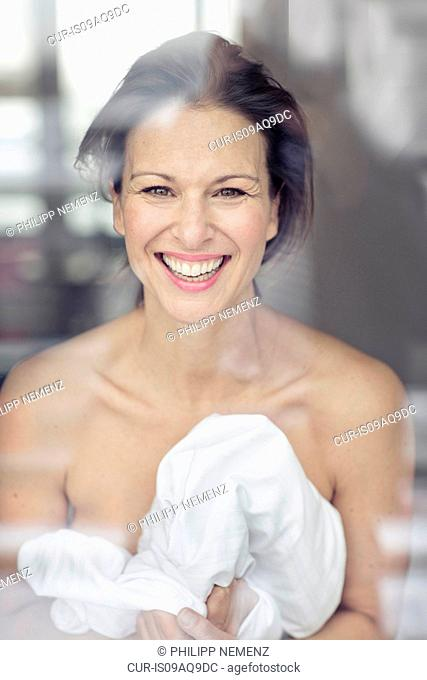 Mature woman wrapped in bed sheet looking out of window