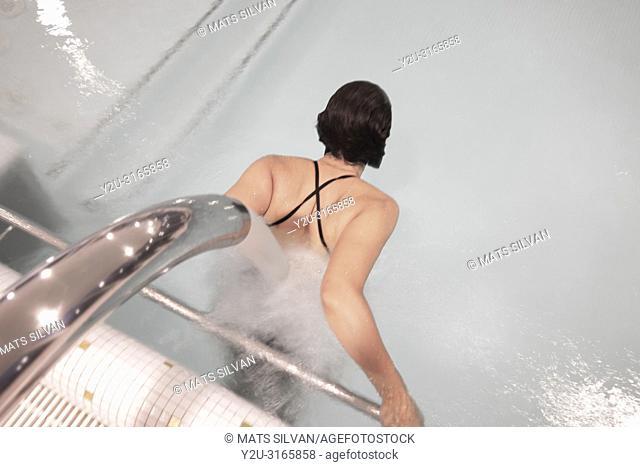 Woman Relaxing in a Hydro Massage Pool with Falling Water on Her Spine in Switzerland