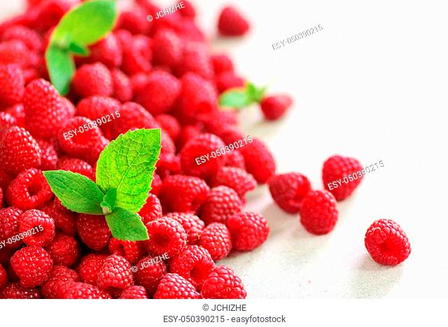 Fresh organic raspberries with mint leaves. Fruit background with copy space. Summer and berries harvest concept. Vegan, vegetarian, raw food