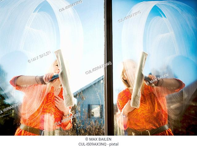 Composite of woman outdoors cleaning windows with squeegee
