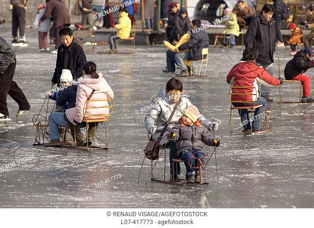 People sliding on ice in chairs on Qianhai Lake. Beijing. China
