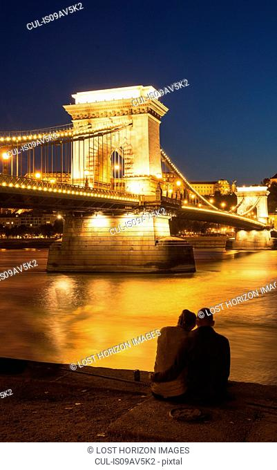 Couple on the Danube bank, Chain Bridge in background, at night, Hungary, Budapest