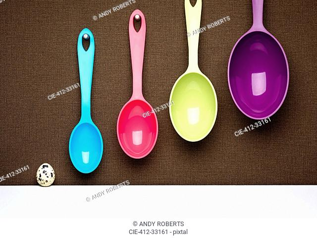 Scale of spotted egg and hanging multicolor measuring spoons
