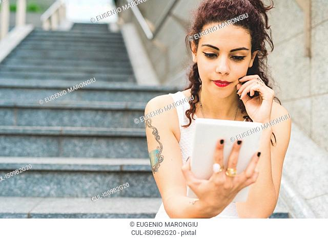 Woman sitting on steps using digital tablet, Milan, Italy