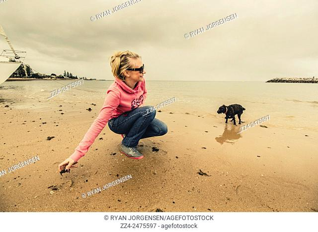 Horizontal wide angle photograph of a blond woman playing with dog on the tideline of coastal Queensland